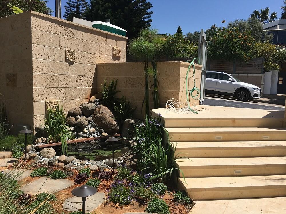 אבני מדרך לגינה משתלבות עם מדרגות אבן וחיפוי כורכר
